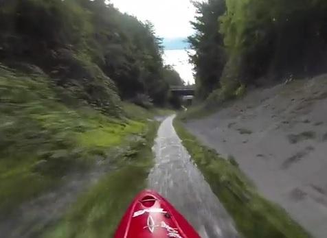 Il descend une rigole en canoë Kayak