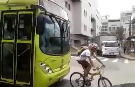 Un cycliste embête un bus en se mettant devant lui