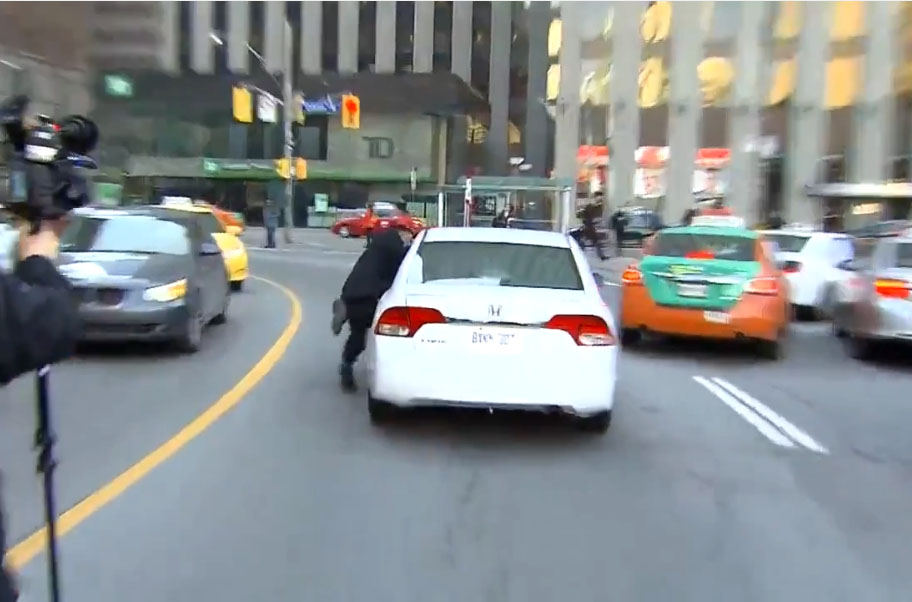Un chauffeur de taxi reste accroché à la portière d'un chauffeur Uber