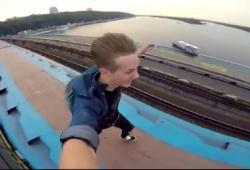 Un jeune homme se met debout sur le toit d'un train en marche