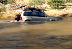 Un Nissan Patrol tente de traverser une rivière avec un courant fort
